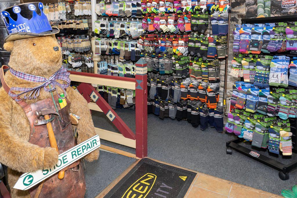 Shoe Repair Bear in front of wall of socks
